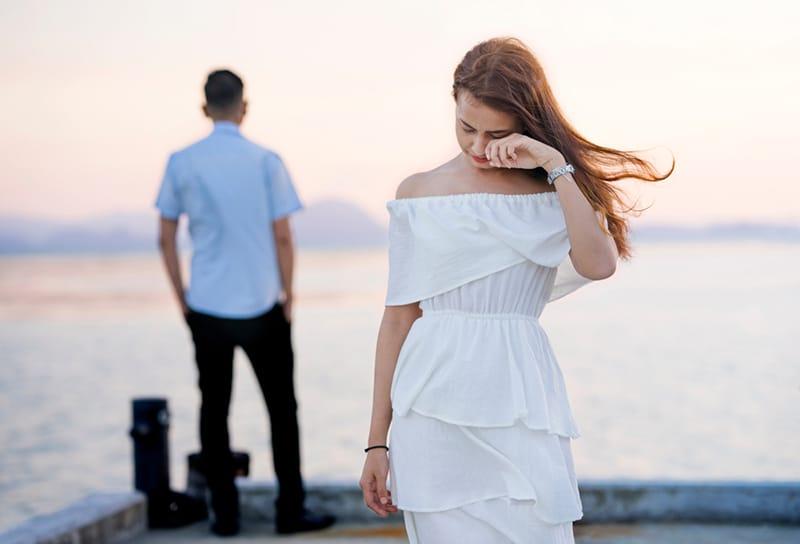 eine weinende Frau, die von einem Mann weggeht, der dem Gewässer gegenübersteht