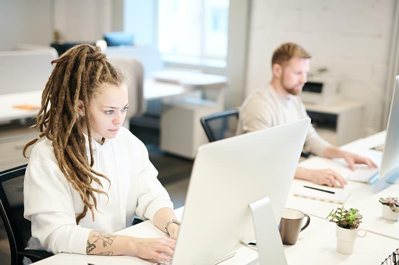 eine wettbewerbsfähige Frau, die neben ihrer Kollegin am Computer arbeitet