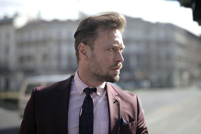 ernsthafter Geschäftsmann, der einen braunen Anzug trägt, der beiseite schaut
