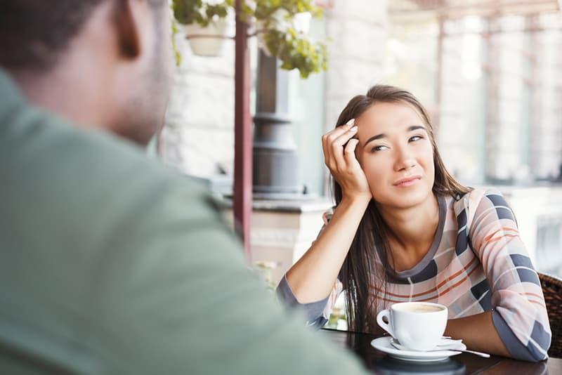 gelangweilte Frau, die einen Mann betrachtet, der über ihr sitzt, während Kaffee zusammen auf einem Date trinkt