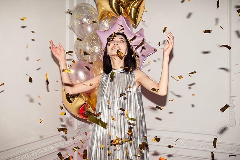 glückliche Frau, die fallendes Konfetti auf ihrer Geburtstagsfeier betrachtet