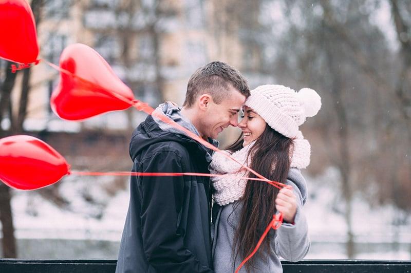 glückliches Paar einander gegenüber während die Frau rote Luftballons hält