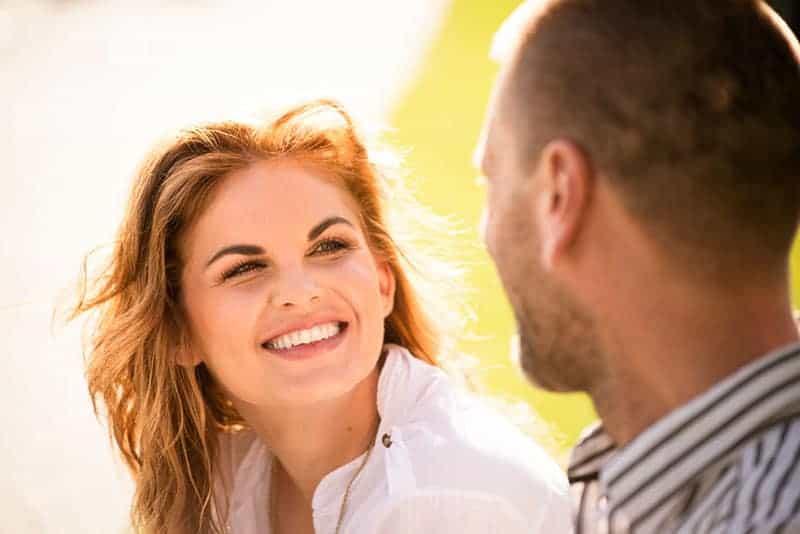 lächelnde Frau, die dem Mann zuhört