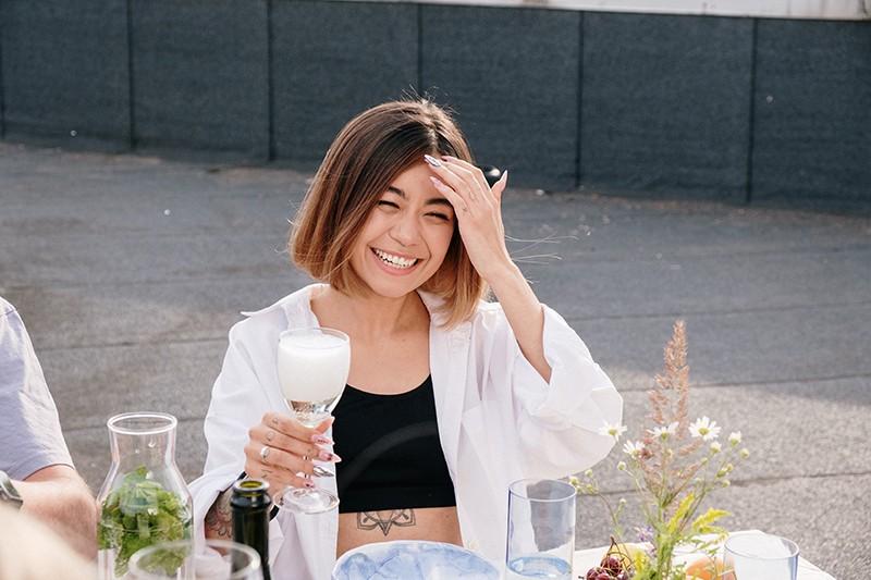 lächelnde Frau, die ein Glas Champagner hält und ihre Haare berührt