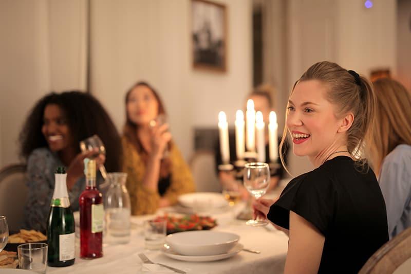 lächelnde Frau, die ein Glas Wein hält, während sie mit Freunden während eines Abendessens sitzt