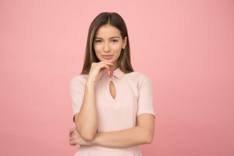 lächelnde Frau, die ein rosa Kleid trägt, das Kinn mit einer Hand berührt