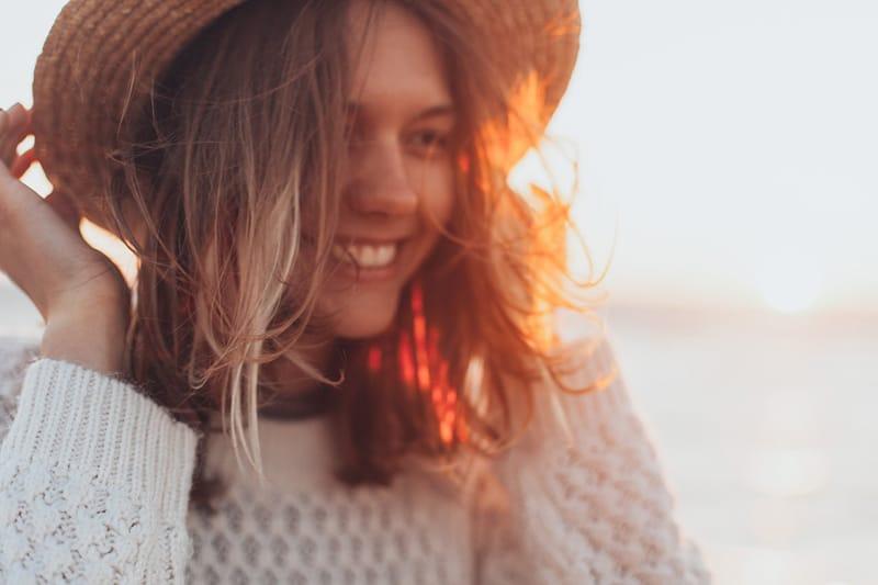 lächelnde Frau, die einen weißen Pullover trägt, der ihren Hut auf dem Kopf hält
