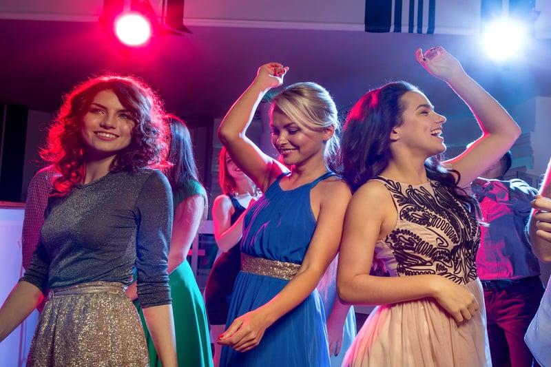 lächelnde Mädchen tanzen in einem Disco-Club