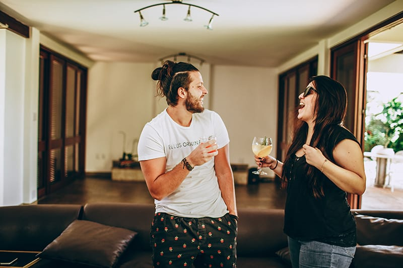 lächelnder Mann und eine Frau, die Getränke hält, während sie im Wohnzimmer sprechen