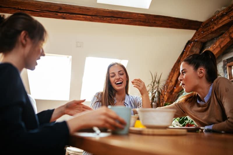 lachende Freundinnen, die zu Hause am Tisch essen