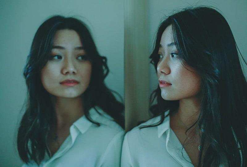 nachdenkliche Frau, die sich in den Spiegel schaut, während sie sich darauf stützt