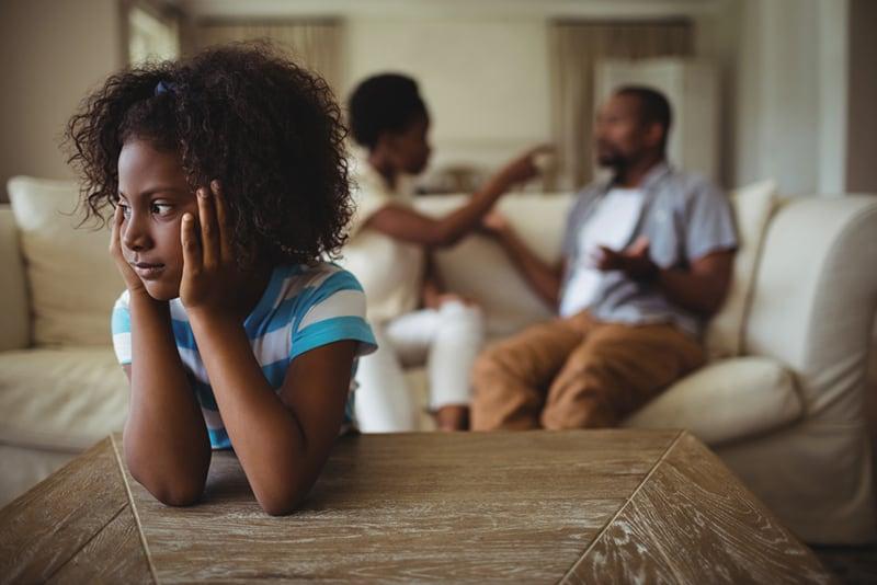 trauriges Mädchen, das ihren Eltern zuhört, die hinter ihr auf der Couch streiten