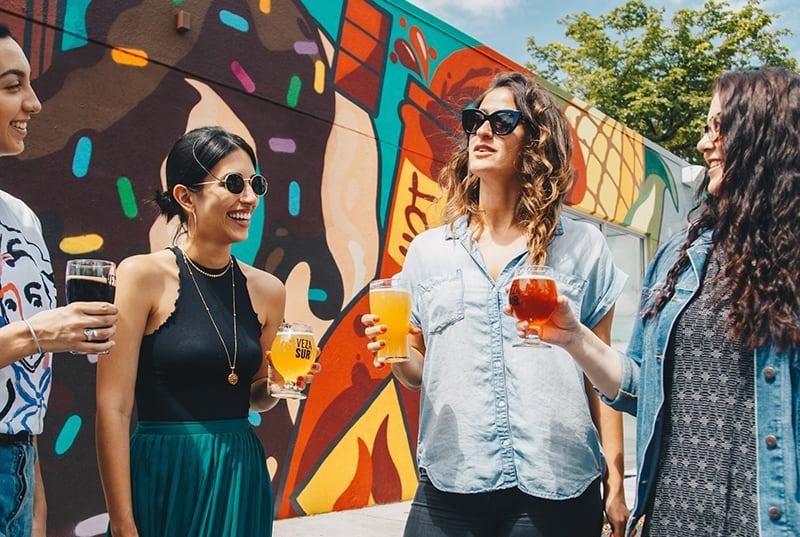 vier Frauen halten Getränke und reden