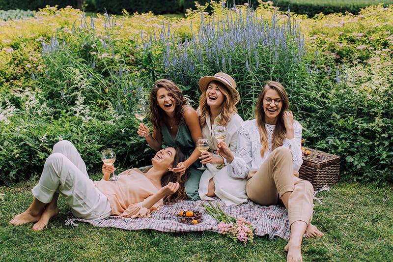 vier lachende Frauen sitzen im Gras und trinken Wein