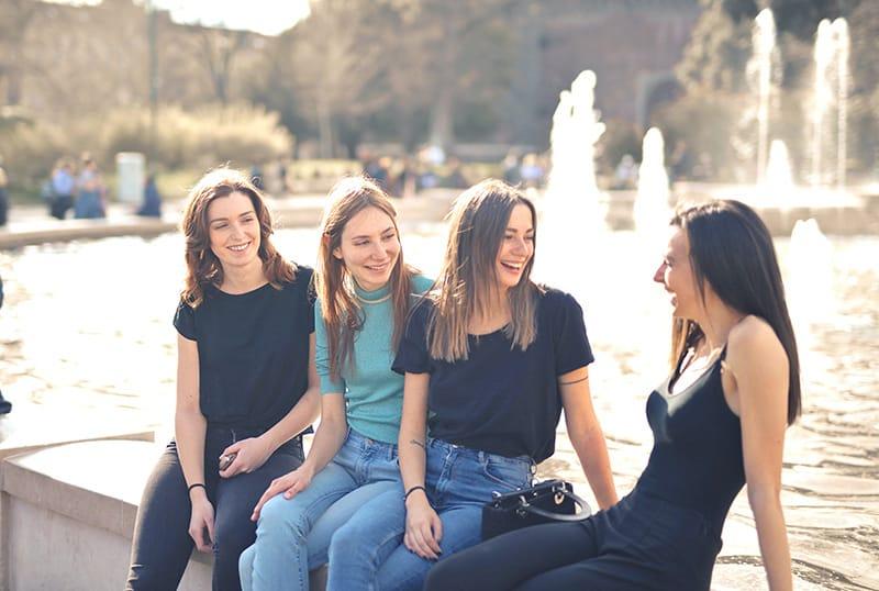 vier lächelnde Freunde, die zusammen rumhängen und in der Nähe des Brunnens sitzen