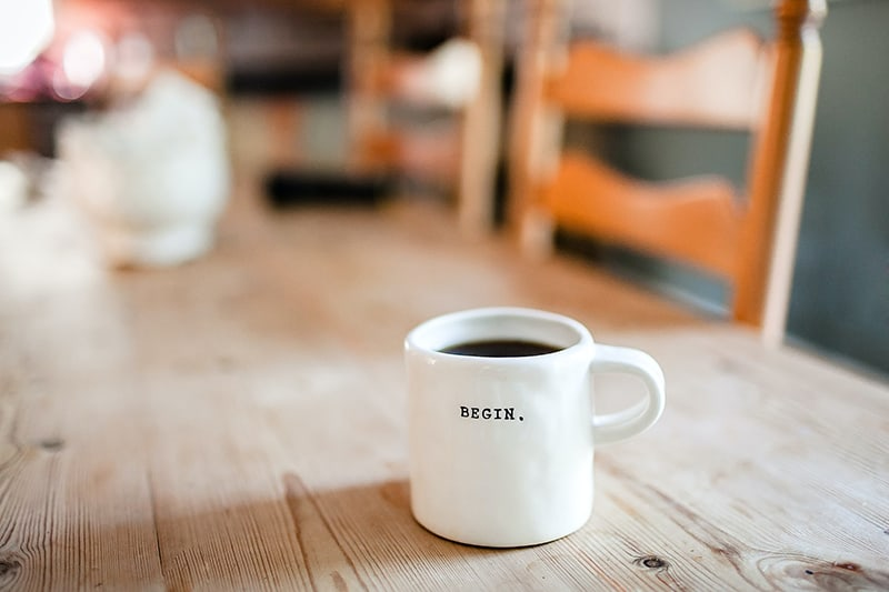 weißer Keramikbecher mit dem Wort Begin auf dem Tisch