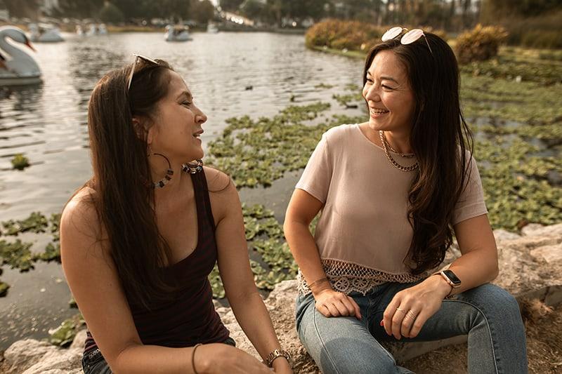 zwei Frauen lächeln und sprechen, während sie in der Nähe des Sees sitzen
