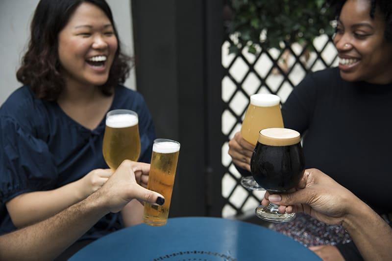 zwei Frauen lachen beim Anstoßen mit Freunden auf ein Bier