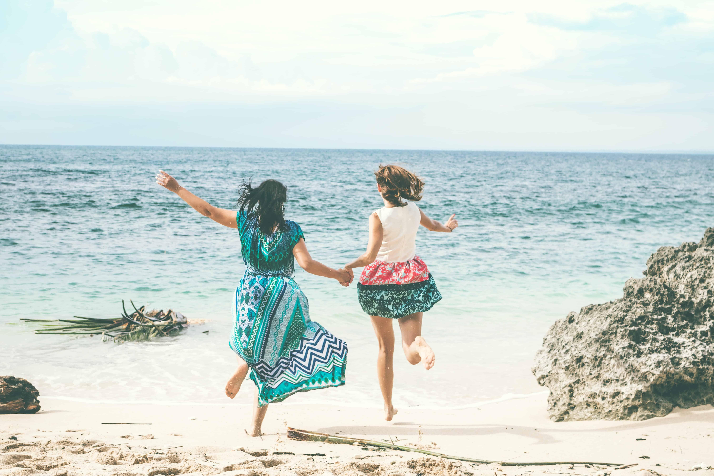 zwei Frauen, die am Strand laufen, während sie Hände halten