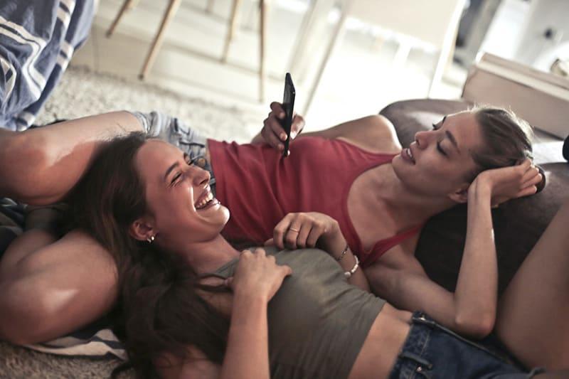 zwei Frauen, die lächelnd auf dem Boden liegen