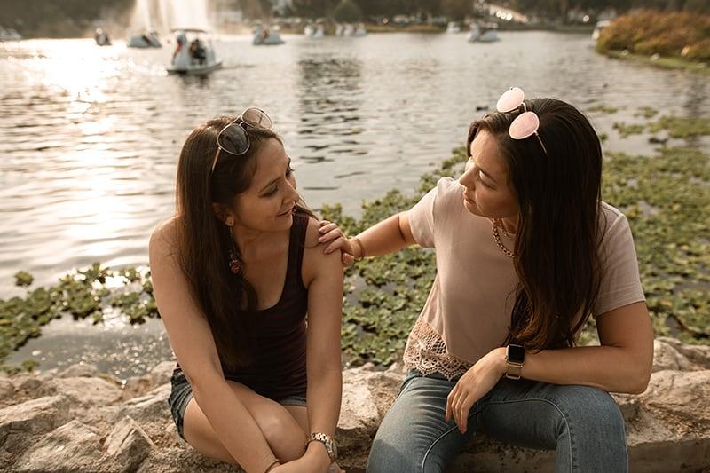 Zwei Frauen unterhalten sich, während sie am See sitzen