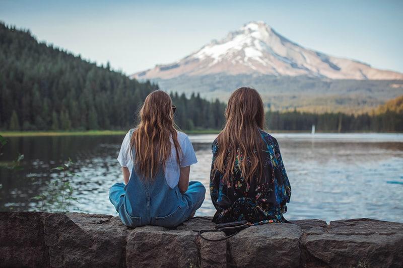 Zwei Frauen sitzen auf dem Felsen und blicken auf den See