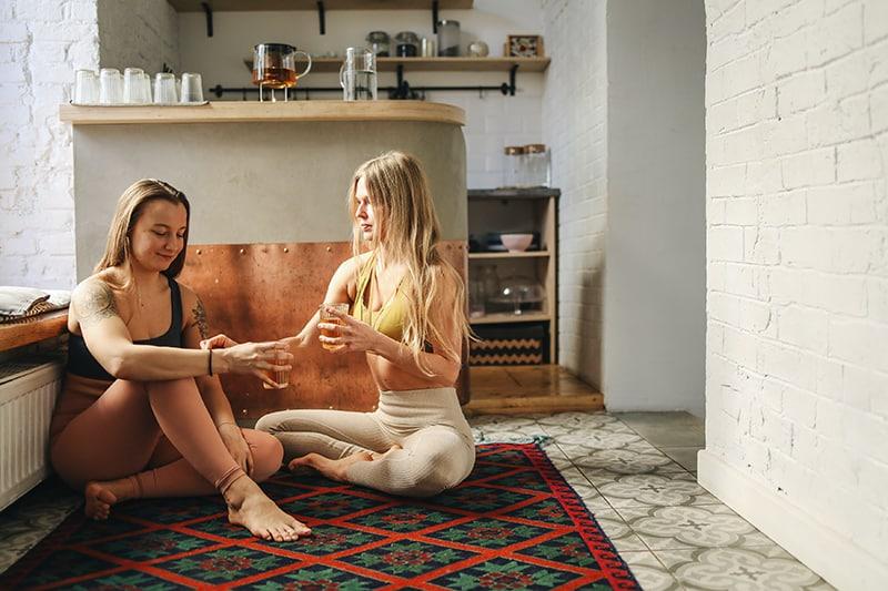 zwei Frauen sitzen auf dem Teppich und halten ihre Getränke