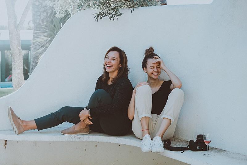 zwei Frauen sitzen auf der weißen Bank und lachen
