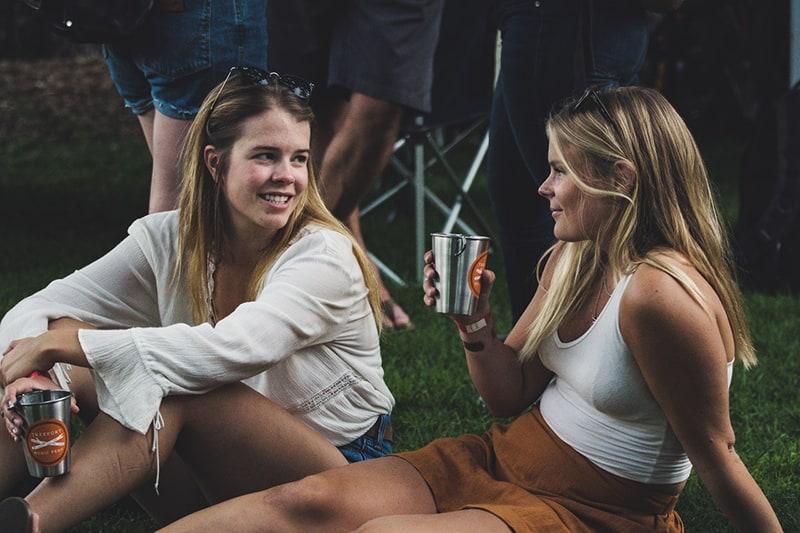 zwei Frauen sitzen im Gras und halten Getränke