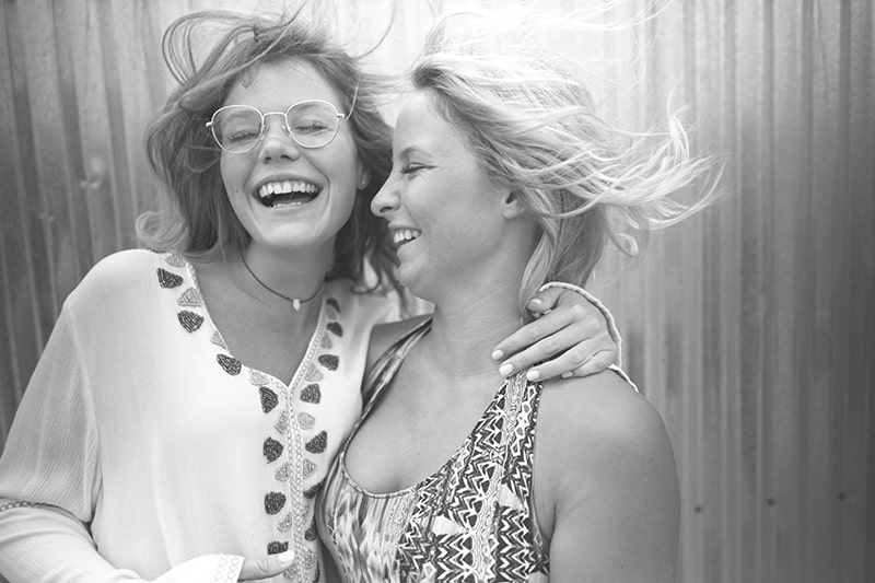 Zwei Frauen umarmen sich und lachen mit geschlossenen Augen