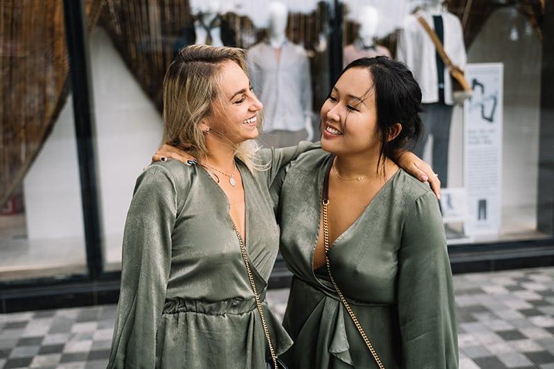 Zwei Frauen umarmen sich und schauen sich an, während sie vor dem Schaufenster stehen