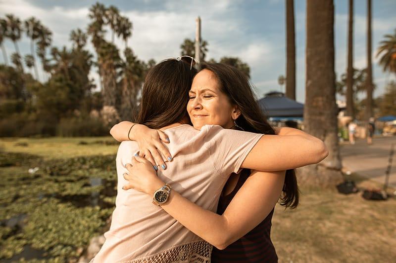 zwei Frauen umarmen sich, während sie im Park stehen