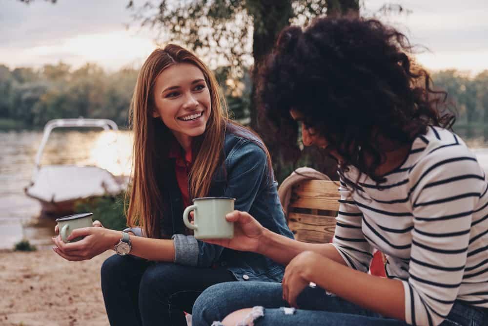 zwei Freunde sitzen in der Natur, trinken Kaffee und reden
