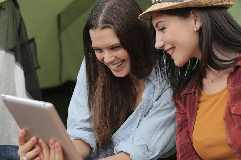 zwei Freundinnen, die eine Tafel betrachten und lächeln