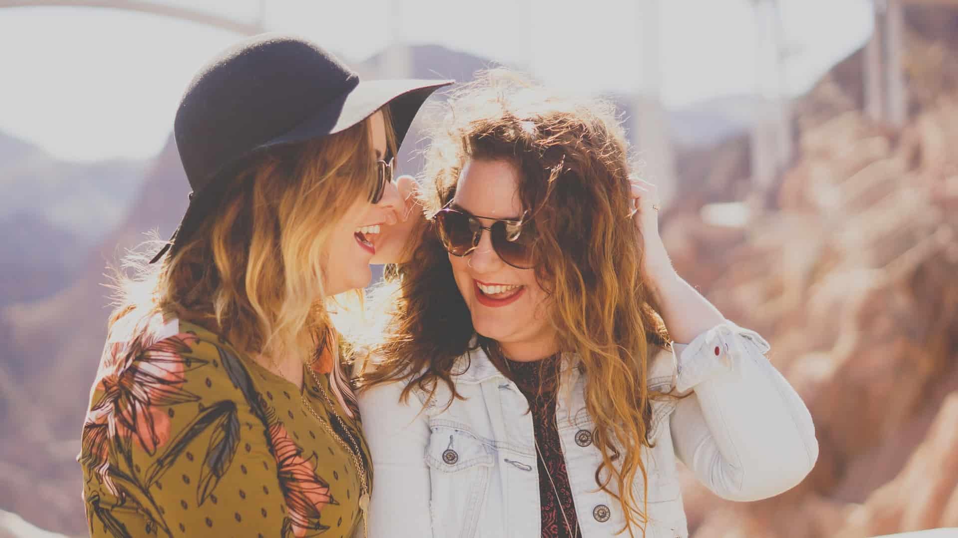 zwei Freundinnen lachen zusammen, während sie draußen stehen