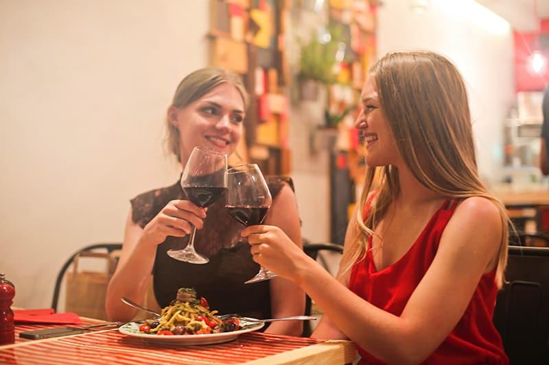 zwei Freundinnen, die während des Abendessens in einem Restaurant mit einem Glas Wein anstoßen