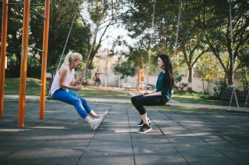 zwei Freundinnen sitzen auf der Schaukel und lachen zusammen
