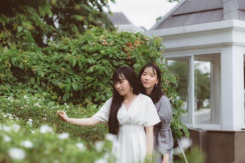 zwei Freundinnen, die tagsüber im Garten stehen