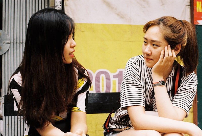 zwei Freundinnen sprechen, während sie auf der Bank sitzen