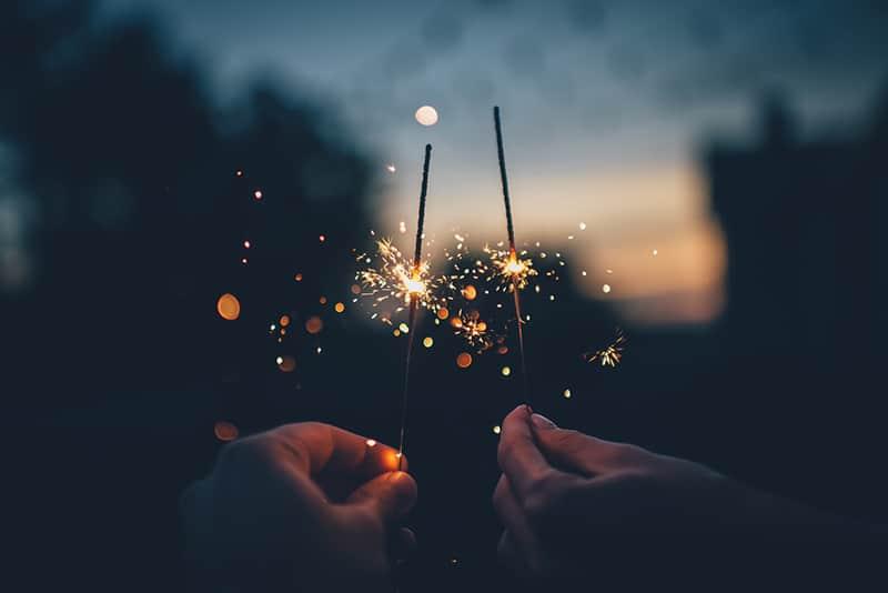 zwei Leute, die nachts Feuerwerk halten