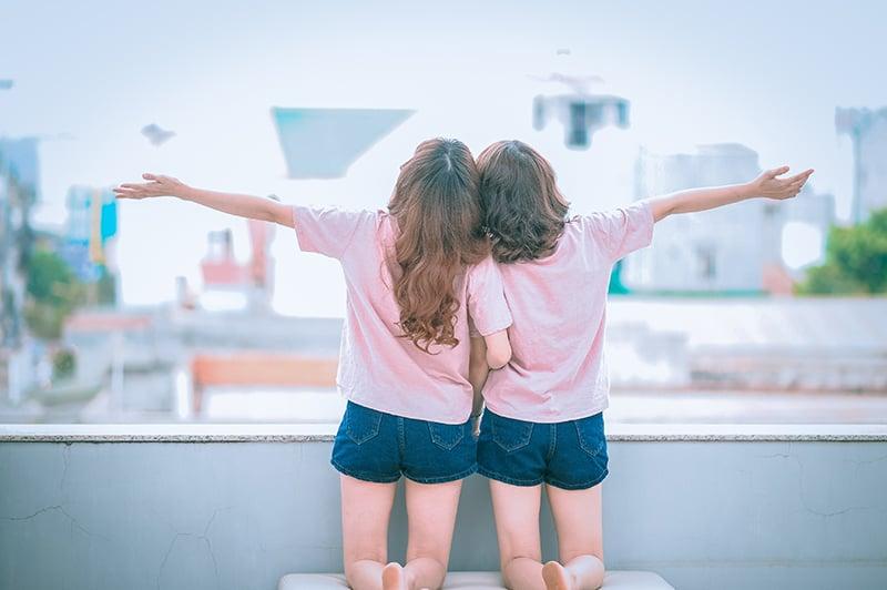 zwei Mädchen, die beim Knien die Arme zusammenbreiten