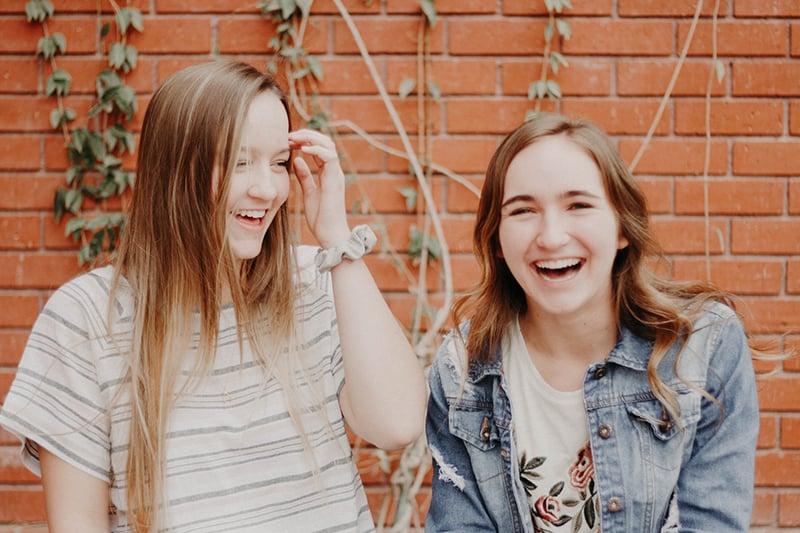 zwei Mädchen, die zusammen lachen, stehen nahe der Mauer