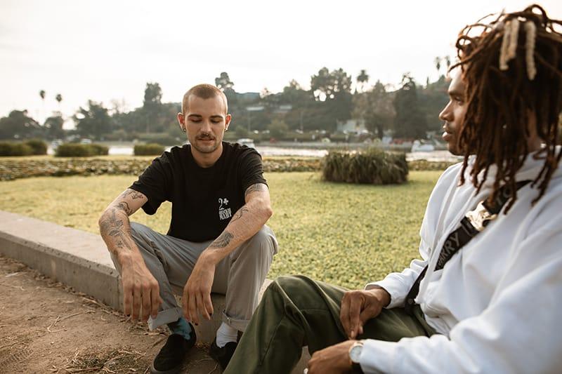 zwei Männer sitzen auf der Betonbank im Park