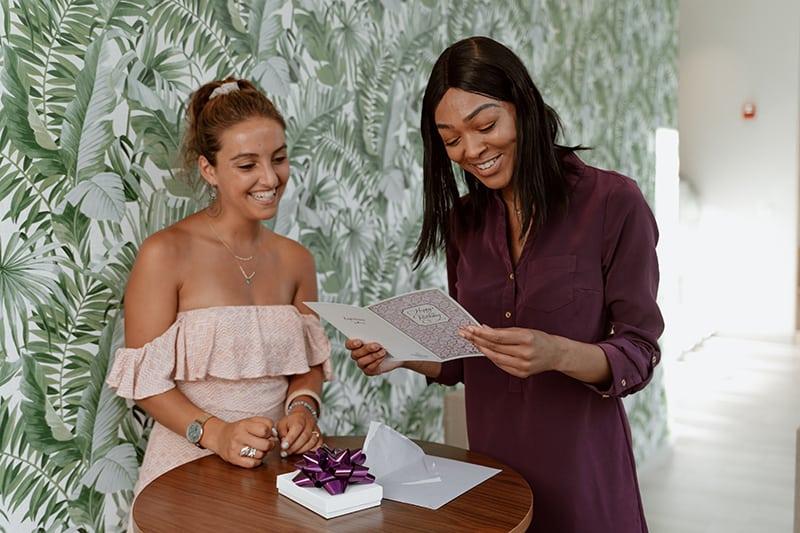 zwei lächelnde Frauen, die eine Geburtstagskarte lesen, während sie am Tisch stehen