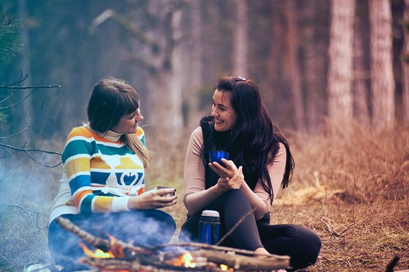 zwei lächelnde Frauen, die nahe dem Feuerknochen sprechen, während sie auf dem Boden sitzen