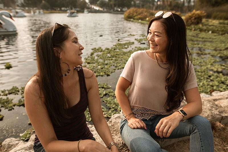 zwei lächelnde Frauen, die sich ansehen, während sie in der Nähe des Sees sitzen