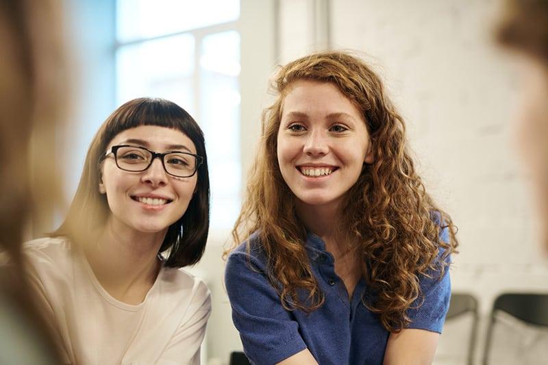 zwei lächelnde Frauen, die beiseite schauen, während sie zusammen sitzen