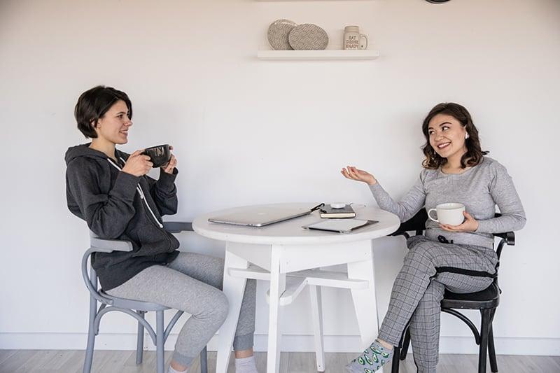 zwei lächelnde Frauen, die sprechen, während sie Tee zusammen am Tisch trinken