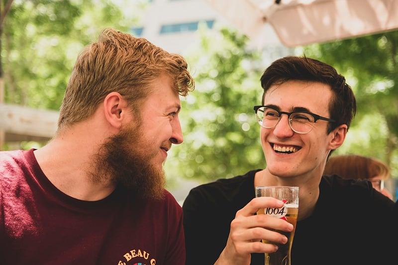 zwei lächelnde Freunde, die sich beim Biertrinken ansehen