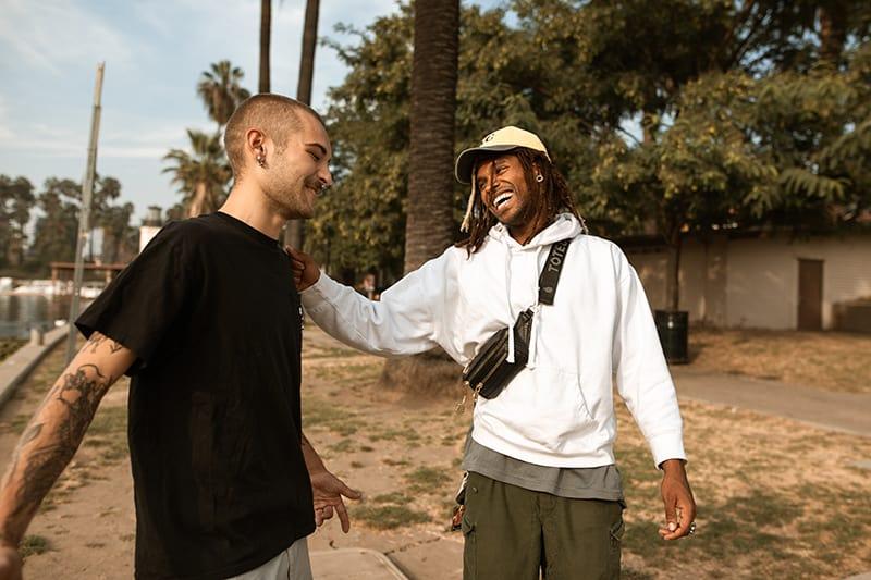 zwei lächelnde Freunde, die im Park sprechen